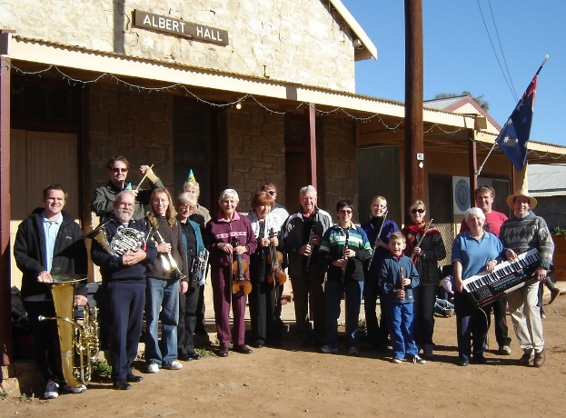 Broken Hill orchestra members standing in front of Albert Hall, Tibooburra