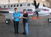 Presenting cheque to Royal Flying Doctor Service, in front of a plane in RFDS hanger